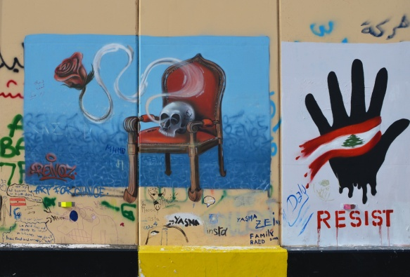 a skull sits on a red upholstered chair with wood arms and legs, on a blue background, also hand with lebanese flag, and the word resist