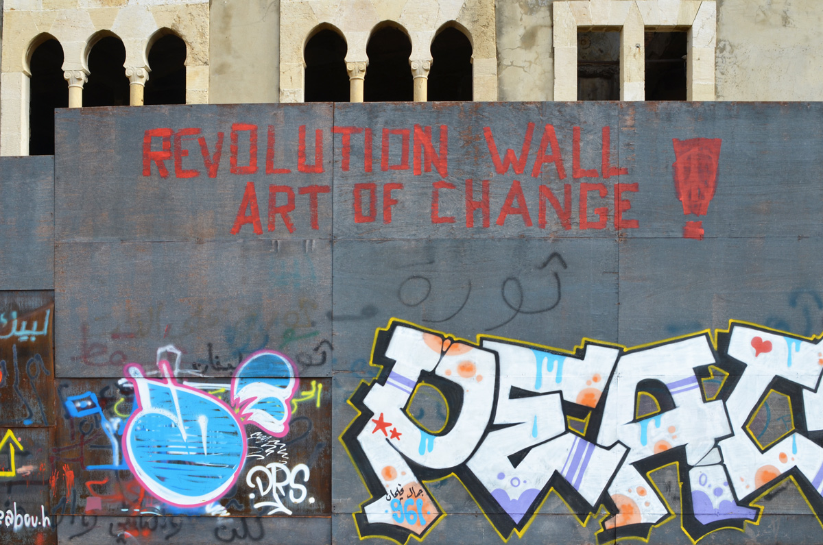 on a grey wall in red letters, Revolution Wall Art of Change, peace written as a tag,