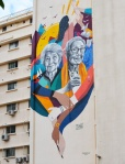 a mural on the side of a building of two older women, Emily Nasrallah and Huguette Caland, with arms linked with extra arms, coloured ribbons winding between and around them
