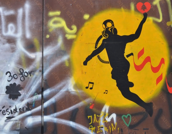 graffiti of a yellow circle with black silhouette of a person with a gas mask on, throwing a red heart