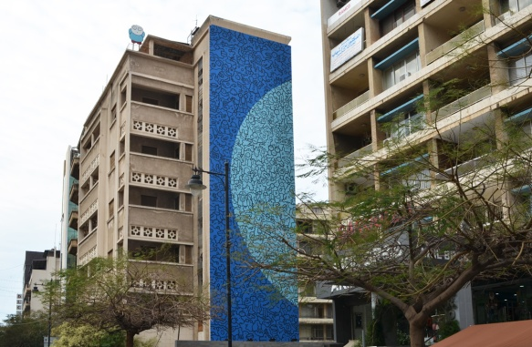 multi storey residential buildings, one has a large mural on the side of it, blue with a lighter blue semi-circle, with black squiggles all over it