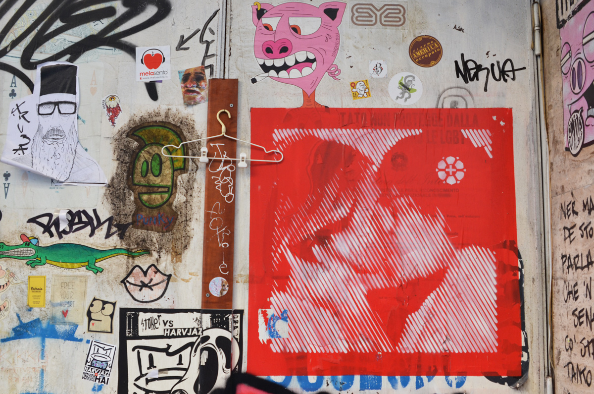 slaps on a wall including a red and white poster of two people kissing