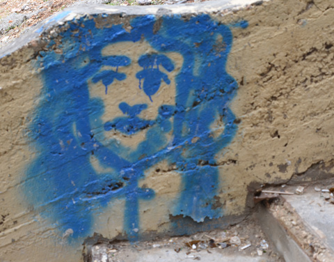 a blue graffiti painting on a wall, down low near the ground, of a man with beard and long hair.