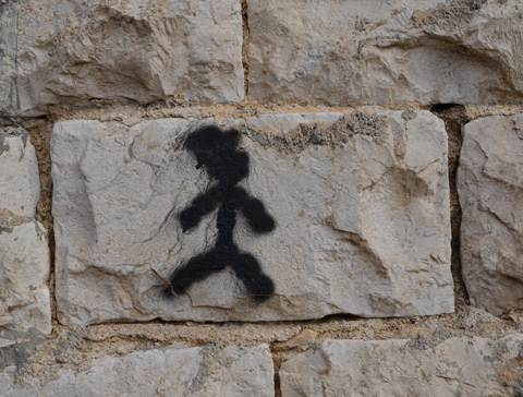 a little black stick figure person painted on a stone wall