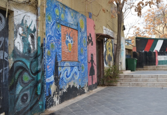 top portion of Kalha stairs in Amman with street art on the walls of the buildings beside the stairs