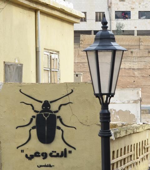 a black beetle graffiti on a yellow wall