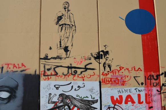 stencil of a man in arab dress walking and other graffiti