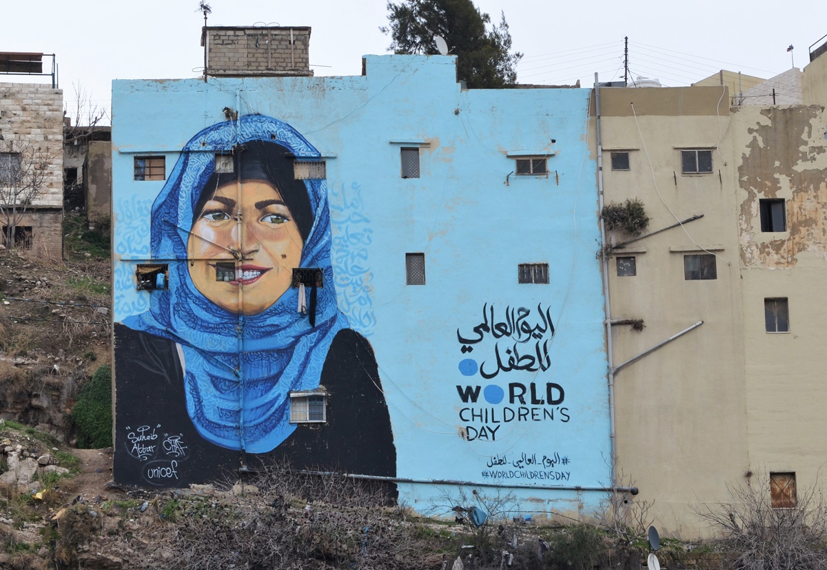 bright blue backkground, on the back of an apartment building, mural, of a woman in blue head scarf, for world children's day, supported by Unicef