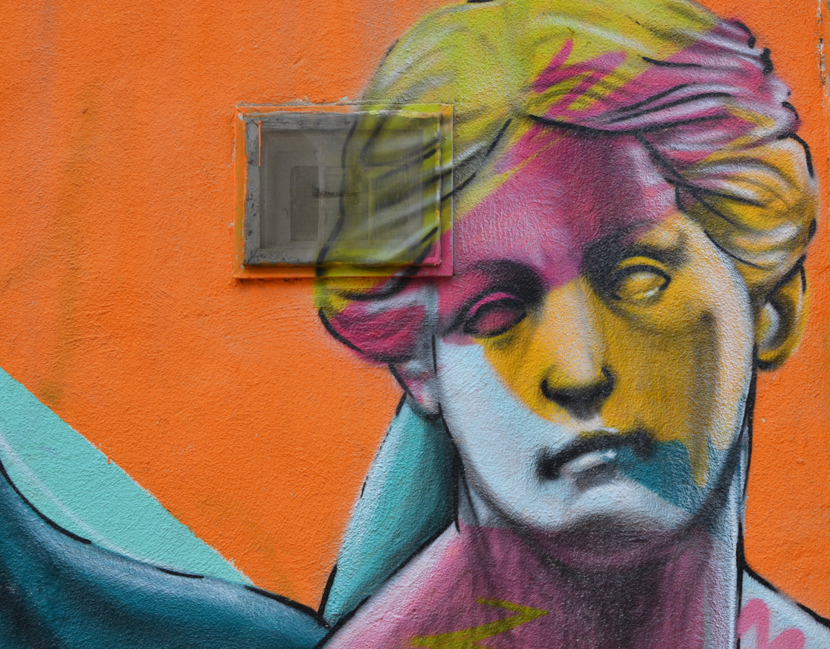 woman's head and shoulders on an orange background, mural by Suhaib Attar, woman is in blue, pink, and yellow splotches. She has wings in the same colour - close up of her face
