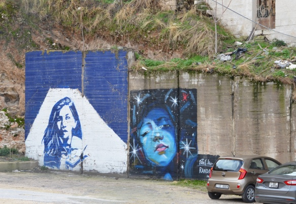 two murals of women. on the left is a portrait in blue and white of a woman with long hair. on the right is a Suhaib Attar painting of a woman's face surroundd by stars
