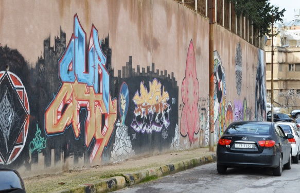 black car parked in front of a brown wall with street art on it, Amman