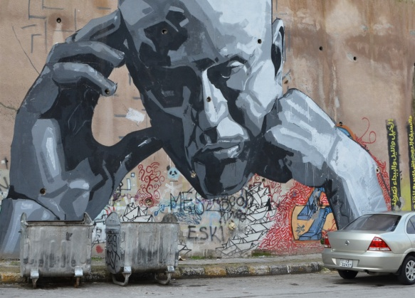 large mural in shades of grey, a man's head, chin on fist and trhe other hand resting on the other side of his head, on a wall, covering some older street art