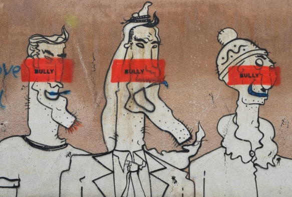 on a brown wall, three comical white characters, male, with exaggerated features drawn in black, each has an orange stripe through their face with the word Bully written on it
