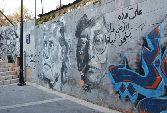 portraits of two men in grey tones, street art on a wall