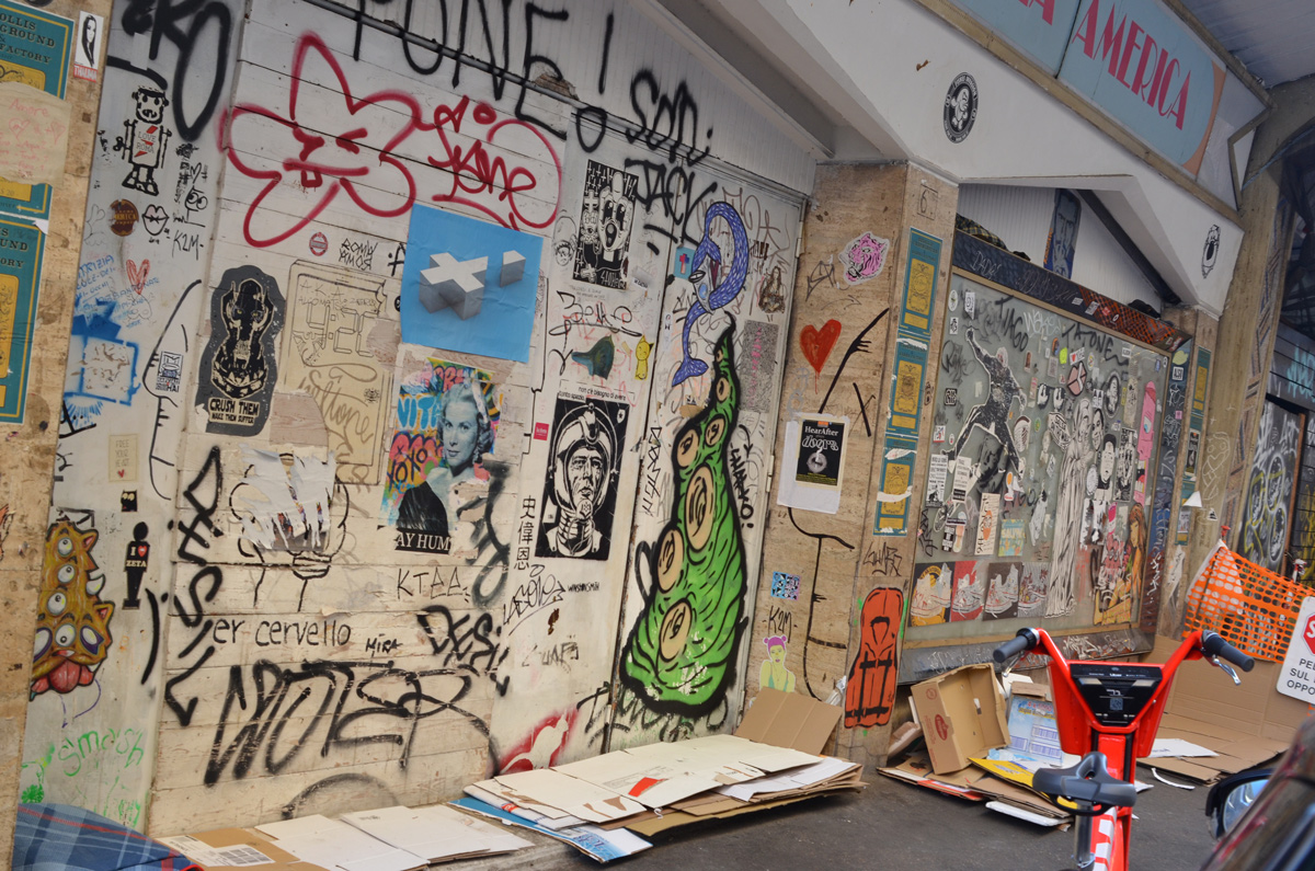 a wall covered with stickers and pasteups