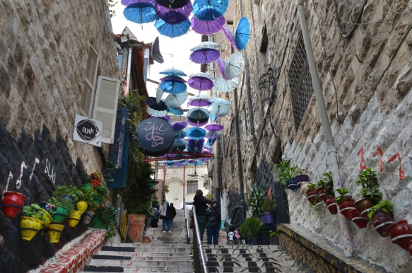 looking up a staircase that is lined with flower pots and covered by many open umbrellas in Amman Jordan