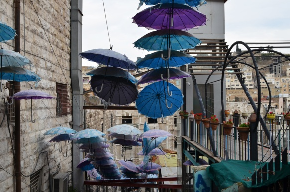 man blue, teal, and purple umbrellas, open, up high to provide shade over a set of stairs in Amman