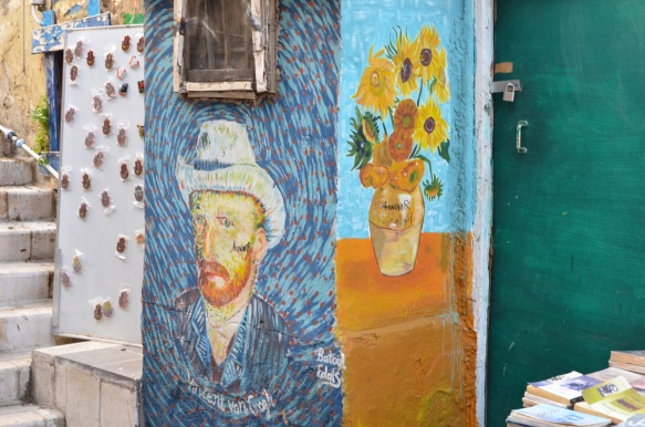 on a wall beside a book store, a copy of Van Gogh's self portrait and a copy of his sunflowers painting, by Batool Edais