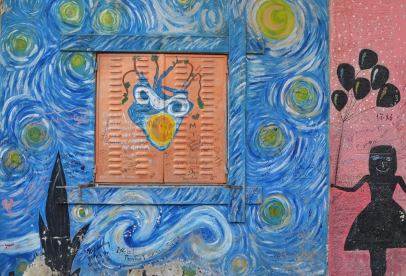 van gogh inspired blue swirls painted in a mural with an orange square in the center. in that square is a heart. To the right of the swirls is a pink vertical bar with a black picture silhouette of a girl holding a bunch of balloons