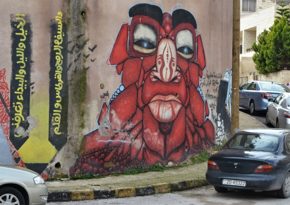 two graffiti pieces, on the left an Arabic verse written vertically and on the right, a red monter head and shoulders,