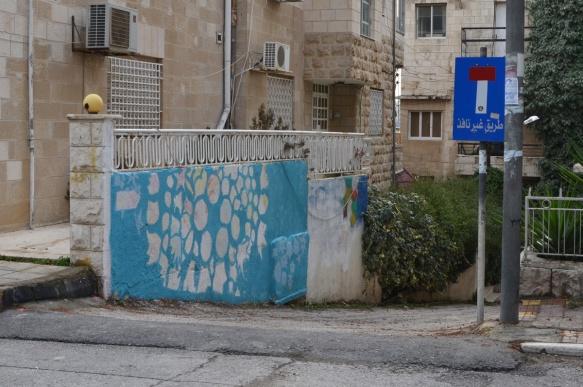 on a wall beside a driveway, a blue and white graffiti