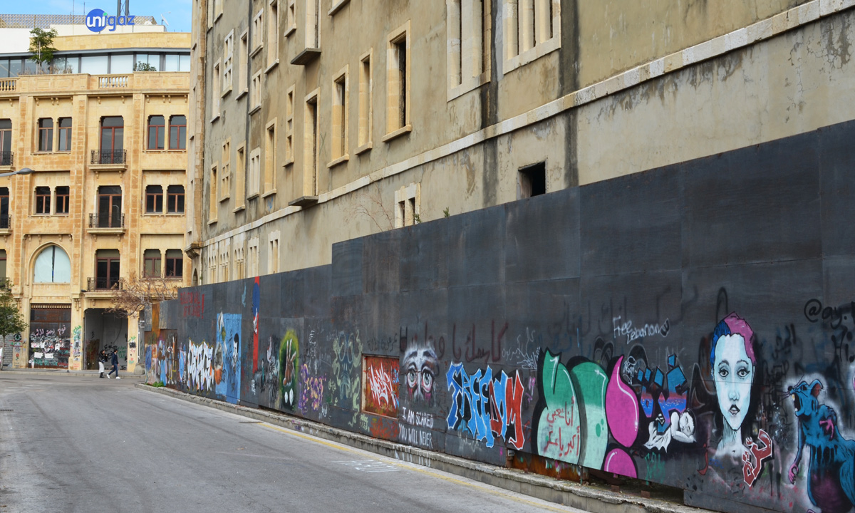 grey wall in front of office building, with street art on the wall, Beirut