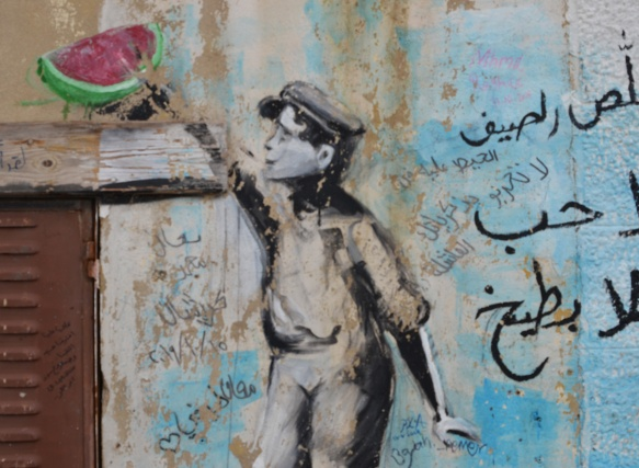 street art painting with Arabic writing, a person reaching for a piece of watermelon up on a shelf