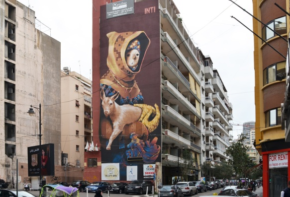 tall Inti mural in Hamras Beirut, of a boy holding onto a goat, boy wearing hooded jacket and a necklace