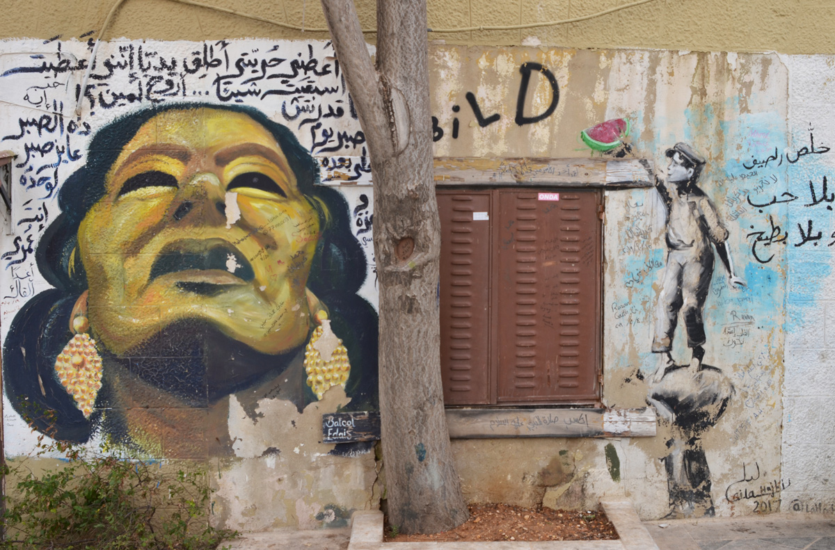 two street art paintings on the sides of a shuttered window. on the left, a gold coloured woman with braids looking to the sky, on the right, a person reaching for a piece of watermelon up on a shelf