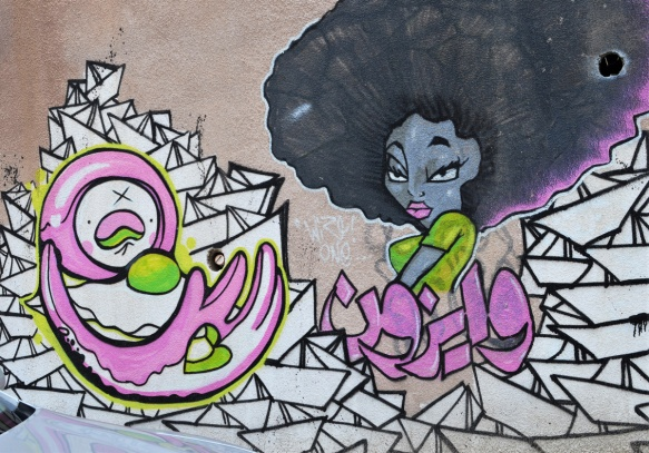 street art on a wall in Amman, a woman with big afro hair by many white paper boats and a character in pink and white, curved arms stylized face