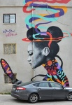large mural in Amman of a woman looking in a hand held mirror, with hair tied in two buns and lots of colourful ribbons around her head