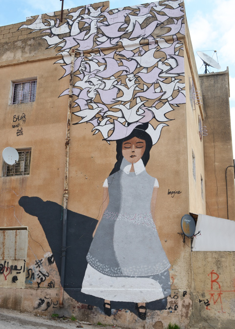large mural of a woman wearing a grey top, eyes closed and dreaming of doves, the title is imagine and it was painted by sourati, on the side of a large building in Amman