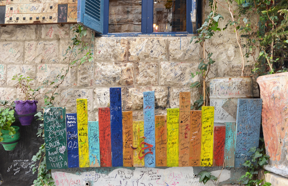 on a wall, under a window with a blue frame, a line of flat pieces of wood painted in bright colours, that look like a row of books