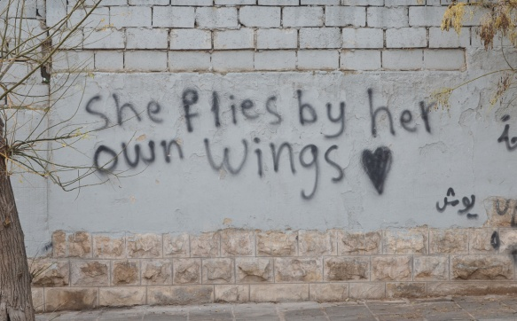 she flies by her own wings, written words painted on a wall, graffiti