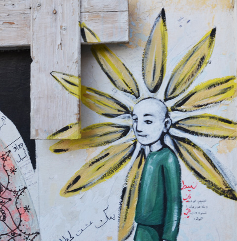 painting of a bald child with green shirt, yellow petals coming out of its head looking like a flower