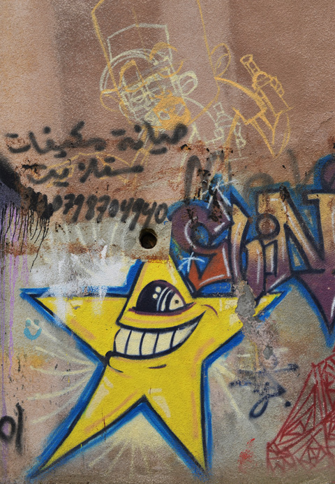 street art on a wall in Amman, a yellow star with an open mouth with big teeth and one eye, looking to the left, Arabic writing and a phone number tag, remnants of a drawing street art