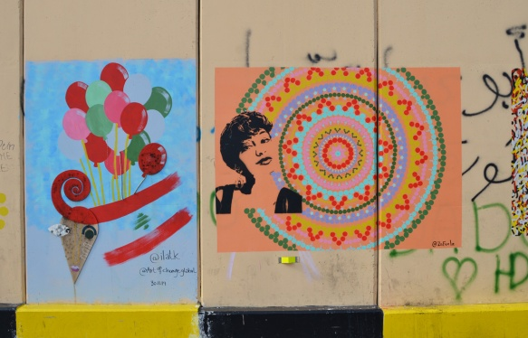 Beirut Revolution Art wall, two pieces, circlar art with woman's face stenciled in black, a painting of balloons and lebanese flag