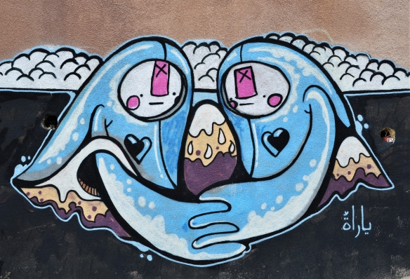 street art on a wall in Amman,- two blue stylized characters with arms curved towards each other and holding hands