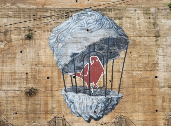 bird in a birdcage that is the shape of a person's head, mural