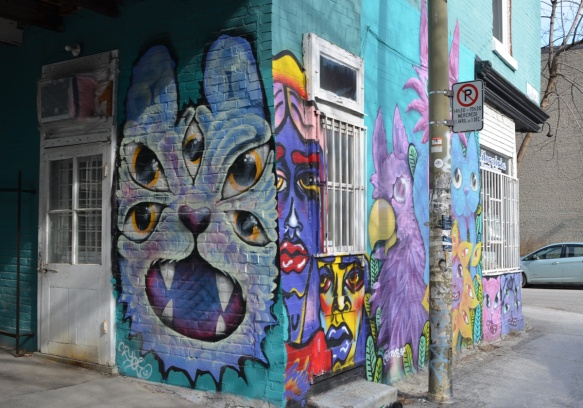 a light purple cat with 5 eyes, mural on a wall, on a corner, with more cats and cats faces on the adjacent wall