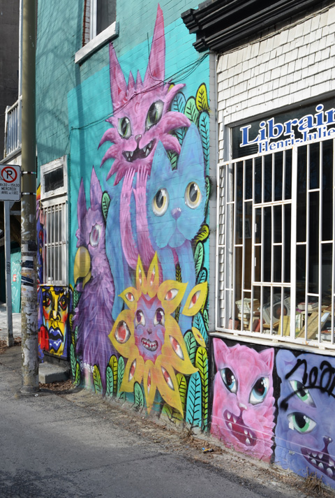 pink and blue cats mural on a wall beside a window, with a pink and blue cat faces under the window