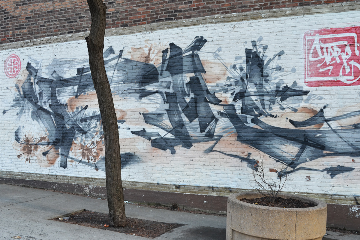 mural on a wall by a sidewalk and small tree, Chinese calligraphy in black and grey, some small pale pink flowers