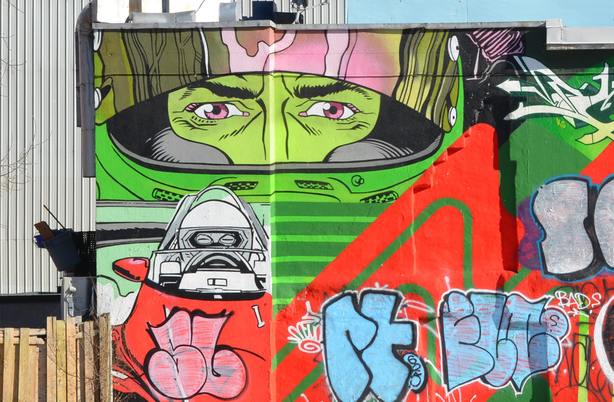 a mural that has been tagged over except for eyes on a green face behind a mask and a black and white figure in a cockpit