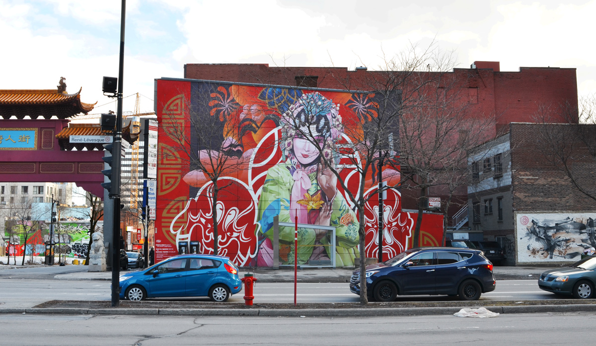 large Chinatown mural of a Chinese woman in flowered costume, with red and white masks on either side of her, one side happy and one side sad. mural is beside a large gate as entrance to Chinatown. Other side of mural is a traditional Chinese paiting with calligraphy and some pink blossoms