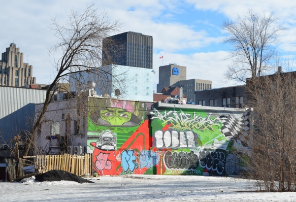 looking across snow covered park to a mural that has been tagged over except for eyes on a green face behind a mask and a black and white figure in a cockpit as well as black and white checkered flag in upper right corner, Montreal buildings behind the mural