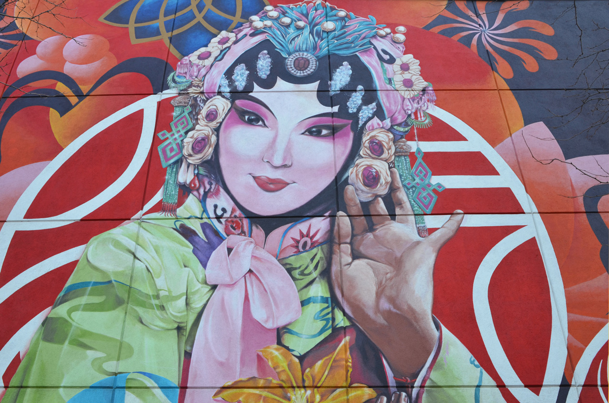 Chinese woman in mural, pink bow at her neck, flowers in her bonnet