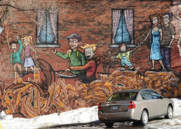 car parked in front of a on the end of a brown brick building, a mural of people walking on large noodles that are coming out of a very large ladle