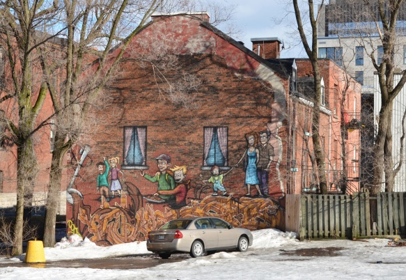 on the end of a brown brick building, a mural of people walking on large noodles that are coming out of a very large ladle