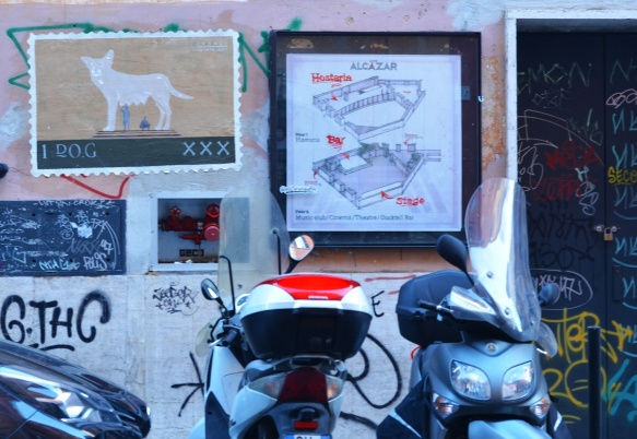 motorcycles parked in front of 2 poster street art pieces. one is a play on Romulus and Remus wolf statue and it is by Gu Tang clan. it is made to look like a postage stamp