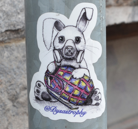 liittle sticker on a grey metal pole, a rabbit in a gas mask holding a hand grenade, dystrastrophy stcker
